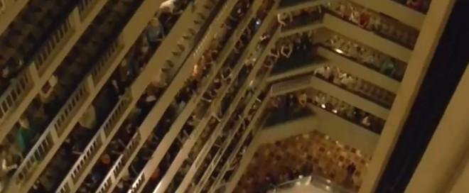 Chorale de centaines d'élèves au balcon d'un hôtel