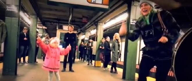 Une fillette danse dans une station de métro