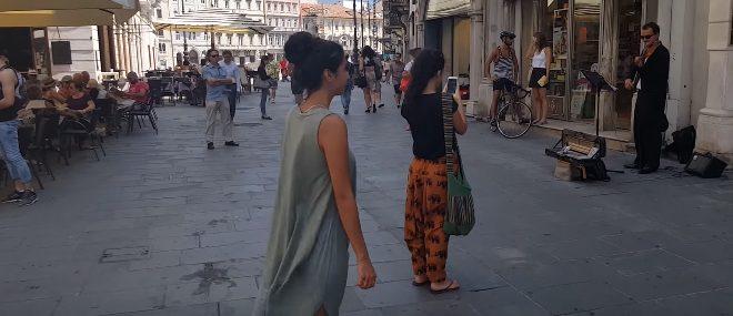Une danseuse accompagne un musicien de rue