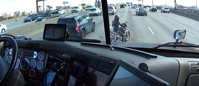 Un camion protège une motarde sur une autoroute